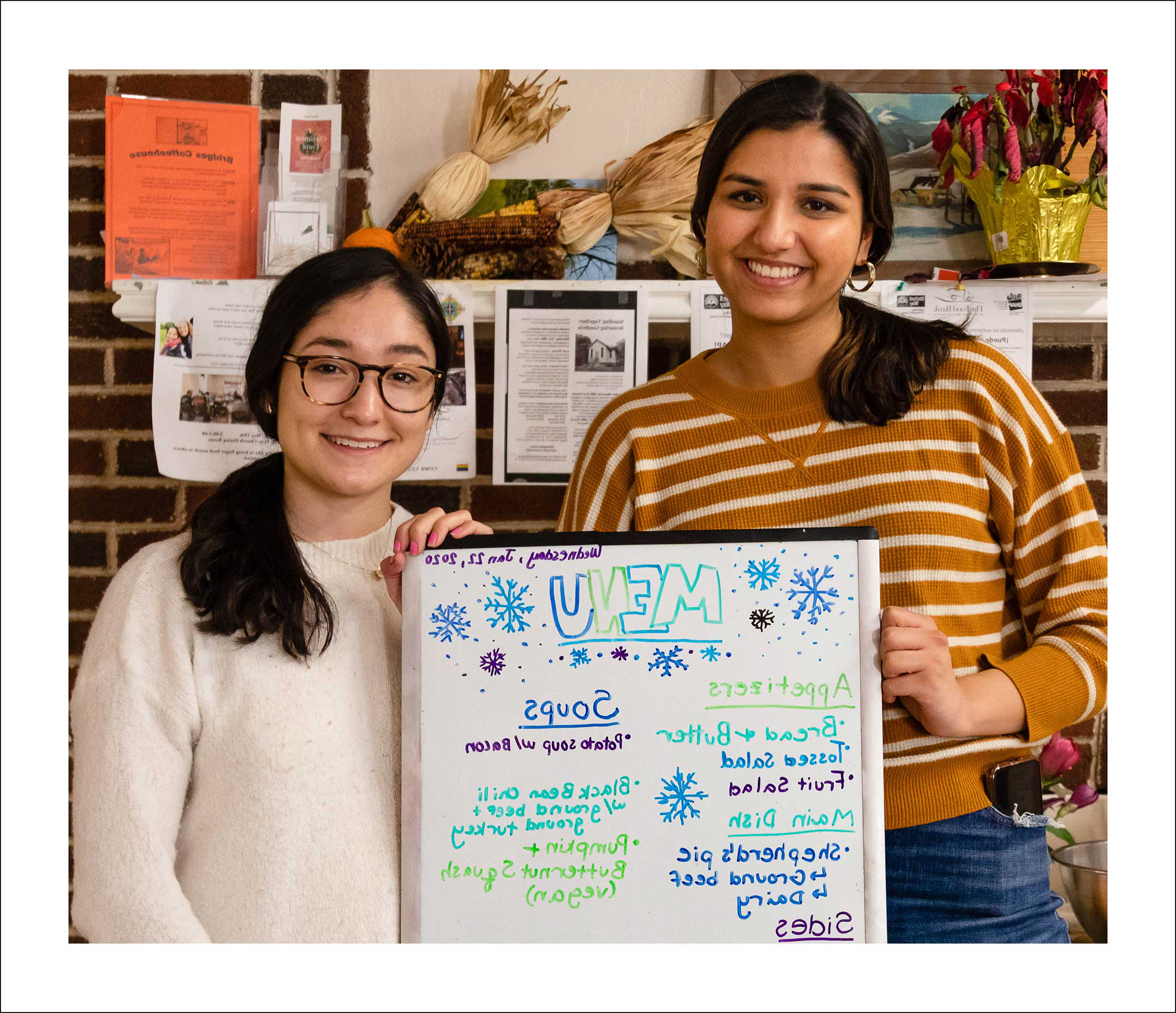 Two women holding a white board covered with writing